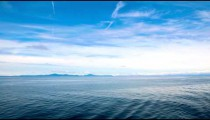 Time lapse of the ocean and blue sky with soft cloud formations, Alaska