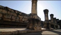 Slow-moving tracking footage of ruined columns in a row near crumbling wall