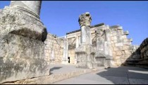 Slow-moving tracking footage of ruined columns near crumbling wall