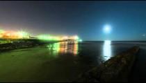 Beach footage of moon setting into the ocean near an Israeli city