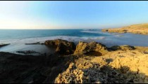 Time lapse of rocky coast on a cloudless day and into night