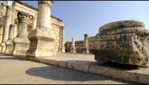 Slow-moving tracking footage of ruined columns in courtyard