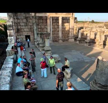Time lapse of tour groups sitting and moving around synagogue ruins