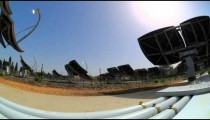 Time-lapse shot behind an array of solar collectors tracking the movement of the sun.