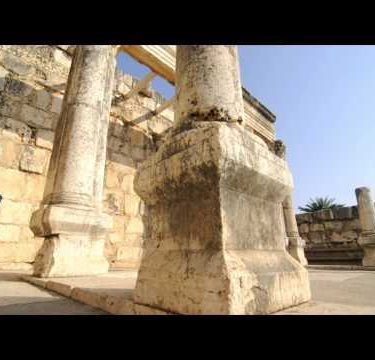 Slow-moving tracking footage of crumbling columns in courtyard