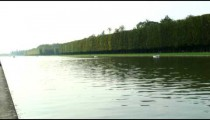 Royalty Free Stock Footage of Looking up a river with boats floating down in Versailles, France.
