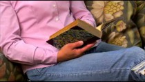 Clip of a woman reading a book on a couch.