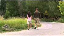 Couple holding hands walking down a pathway.