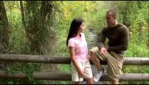 Clip of a couple having a conversation on a bridge.