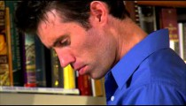 Man in a blue shirt reading a book.