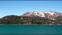 Time lapse view of green, rocky, snow capped mountains surrounded by glassy blue water, Alaska.