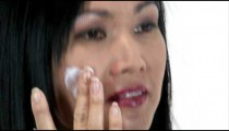 Woman rubbing lotion onto her face.