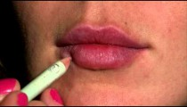 Close up on a woman's lips as she applies lip liner.