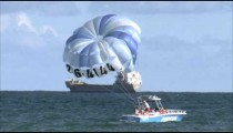 Parasail boat in the ocean with cargo ship in the background.