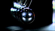 Extreme close up of a Newton's Cradle in motion.