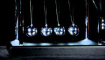 Newton's Cradle balls colliding on black background.