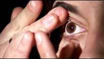 Extreme close up of a woman putting a contact in her eye.