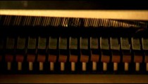 Piano hammers striking strings of a piano.