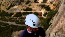 Clip of a mountain climber rappelling down a cliff.
