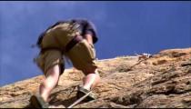 Shot of a rock climber climbing up a cliff.