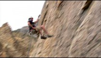 Rock climber hopping across a cliff face.