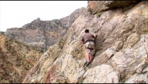 Shot of a rock climber climbing up the face of a cliff.