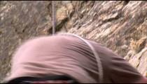 Rock climber climbing down a cliff.