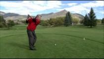 Golfer teeing off.