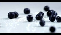 Royalty Free Stock Footage of Blueberries dropping onto a table.