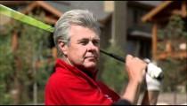 Close shot of a golfer swinging an iron.