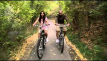 Couple riding their bikes through a tree-covered path.
