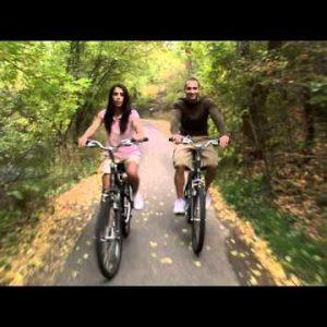 Couple riding their bikes through a tree-covered path.