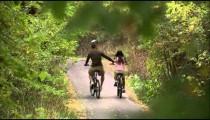 Man and woman riding their bikes through trees.