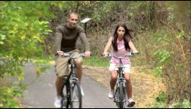 Couple riding bikes down a tree-covered path.