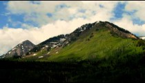 Time-lapse of a mountaintop with snow patches amid greenery.