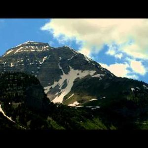 Time-lapse of a high mountain peak with snow patches and clouds.