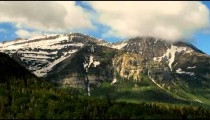 Time-lapse of mountain range with snow patches and clouds.