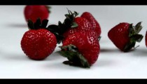 Royalty Free Stock Footage of Strawberries dropping onto a table.