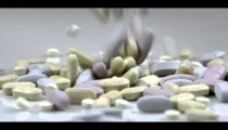 Royalty Free Stock Footage of Supplement pills dropping into a pile.