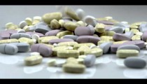 Royalty Free Stock Footage of Supplement pills falling onto a pile.