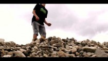 Royalty Free Stock Footage of Young man bouncing a soccer ball on his head on a pile of rocks.
