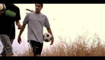 Royalty Free Stock Footage of Two boys walking through a field carrying soccer balls.
