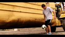 Royalty Free Stock Footage of Juggling a soccer ball in front of a large tractor.