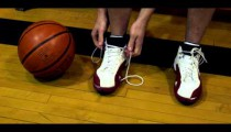 Royalty Free Stock Footage of Young man tying basketball shoes.