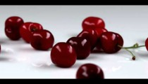 Royalty Free Stock Footage of Red cherries falling onto a table.