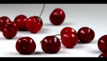 Royalty Free Stock Footage of Red cherries being dropped onto a table.