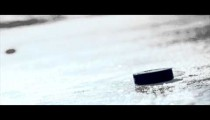 Royalty Free Stock Footage of Hockey puck falling onto ice and being picked up by a gloved hand.