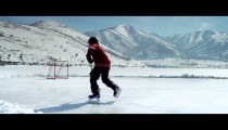 Royalty Free Stock Footage of Young boy playing hockey at an outdoor rink.