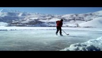 Royalty Free Stock Footage of Young boy dribbling a hockey puck back and forth at an outdoor rink.