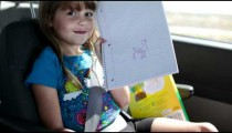 Little girl draws a picture while riding in a car